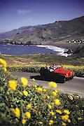 """Weekend getaway"". Red Jeep on northern California coast road in Marin County. MODEL RELEASED."