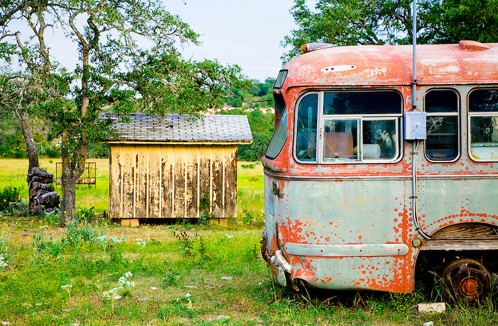 Broken down, rusted bus stranded on a ranch in the Texas Hill Country.