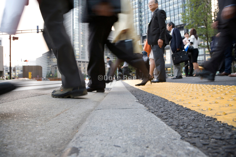 business men and women stepping on to a zebra crossing with one elderly person waiting