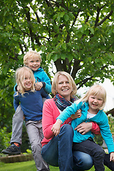 Mother playing garden with young kids piggyback