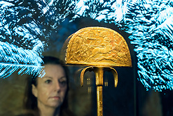 """© Licensed to London News Pictures. 01/11/2019. LONDON, UK. A woman views """"A Gilded Wooden Ostrich Hunt Fan"""".  Preview of """"Tutankhamun, Treasures of the Golden Pharoah"""" at the Saatchi Gallery in Chelsea.  The exhibition celebrates the 100th year anniversary of the opening of Tutankhamun's tomb and displays 150 works in the largest collection of Tutankhamun's treasures ever to leave Egypt.  The show runs 2 November to 3 May 2020.  Photo credit: Stephen Chung/LNP"""