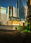 Lone cyclist passing the City of London skyline and building work seen from Fenchurch Street, on 16th April 2020 in London, United Kingdom. Normally crowded with people London is like a ghost town as workers stay home under lockdown during the Coronavirus pandemic. The green glow comes from sunlight reflected from green tinted windows of one of the overlooking modern buildings.