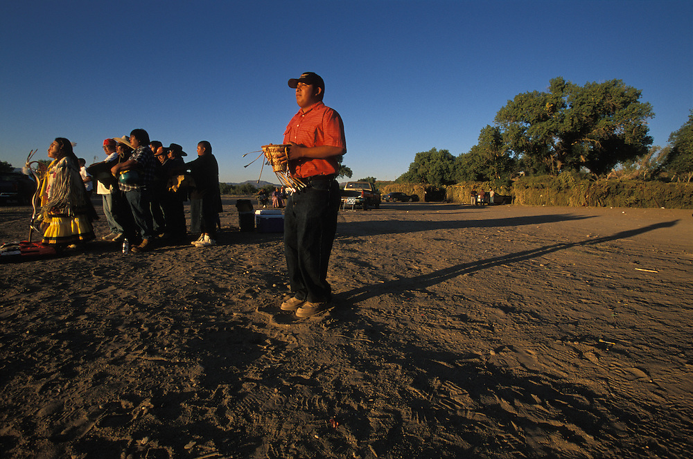 A Group of Apache Indians dance at a Sunrise Dance, the first menstruation ceremony of an Apache girl, on the San Carlos Apache Indian Reservation in Arizona, USA. Behind the girl, who is dressed in buckskin clothes, the medicine man and his helpers sing and beat their drums. The Sunrise Dance is held during the summer, within one year after the girl has had her first menstruation, and lasts for four days. The ceremony is an enactment of the Apache creation myth and during the rites the girl 'becomes' Changing Woman, a mythical female figure, and comes into possession of her healing powers. The rites are also supposed to prepare the girl for adulthood and to give her a long and healthy life without material wants.