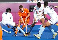 LONDEN - Sander de Wijn tussen drie Indiers, maandag in de hockey wedstrijd tussen de mannen van Nederland en India (3-2) tijdens de Olympische Spelen in Londen .ANP KOEN SUYK