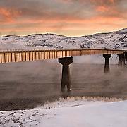 A bridge spanning the Gunnison River in Colorado at twilight.