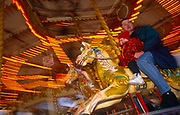 A father and his young daughter ride a merry-go-round on the sea front at Southport, Merseyside, northern England. Hanging on to the carousel's horse, the little girl grips her dad's hand as they whiz along enjoying each other's company.  A background sign tells riders to pay 50 pence per person on each carousel horse which is a brightly-coloured animal looking as traditional as possible. The background blurs but we see the bright lights above the pier's amusement arcade entrance (the second longest pier in the UK) but it is a chilly winter, an off-season day with few people about on this chilly day nearing Christmas.