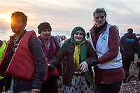 LESVOS, GREECE - FEBRUARY 09: A refugee and a volunteer help Sara to get off a dinghy where she arrived with her son and grandsons after crossing the Aegean sea from the Turkish coast on February 09, 2015 in Lesvos, Greece. Photo: © Omar Havana. All Rights Are Reserved
