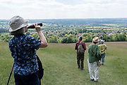A thirsty woman drinks from her water bottle as a group of walking friends on a public footpath, descend the contours of the escarpment that overlooks the Kent village of Kemsing, on 13th June 2021, in Kemsing, Kent, England.