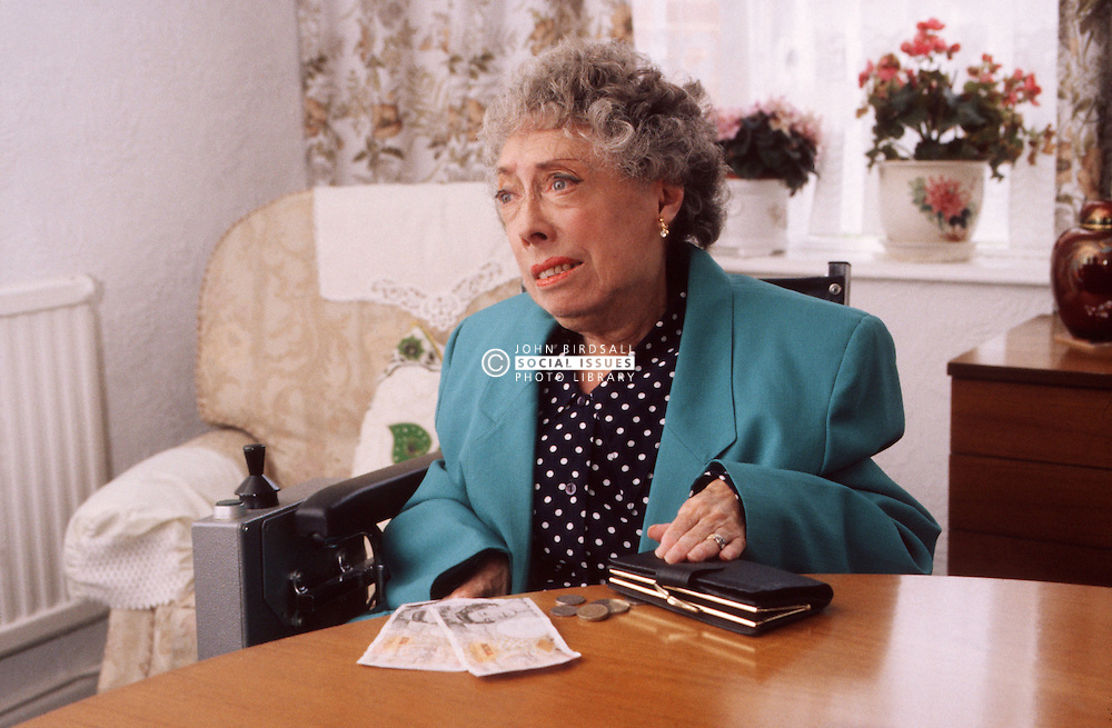 Elderly woman with disability; who is wheelchair user; counting money,