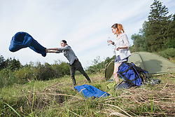 Teenage boy shaking sleeping bag in front of camp tent in forest, Bavaria, Germany