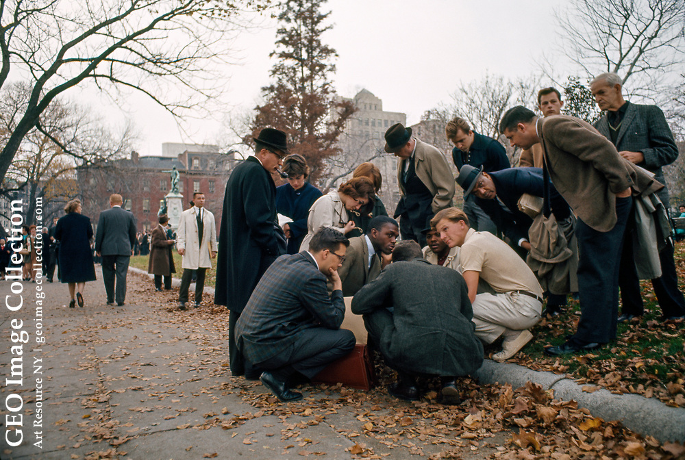 Men conversing along a curb during the funeral of President Kennedy.