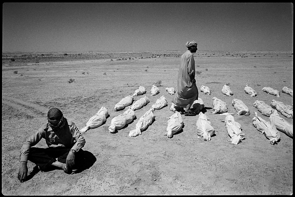 Bones and clothes lie in the shrouds in the desert at a mass grave near Al-Musayab, Iraq. After exhumation, the bodies will be displayed in town to allow people to look for their relatives.