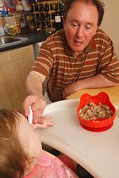 Grandfather feeding baby in kitchen
