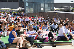 © Licensed to London News Pictures. 07/07/2017. LONDON, UK.  Office workers relax and watch Wimbledon tennis on a big screen at lunchtime near St Paul's Cathedral in London during hot and sunny weather today.  Photo credit: Vickie Flores/LNP