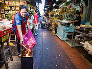 27 JANUARY 2017 - BANGKOK, THAILAND: A woman in a Chinese market burns ghost money for her ancestors on Chinese New Year day in Bangkok. 2017 is the Year of the Rooster in the Chinese zodiac. This year's Lunar New Year festivities in Bangkok were toned down because many people are still mourning the death Bhumibol Adulyadej, the Late King of Thailand, who died on Oct 13, 2016. Chinese New Year is widely celebrated in Thailand, because ethnic Chinese are about 15% of the Thai population.       PHOTO BY JACK KURTZ