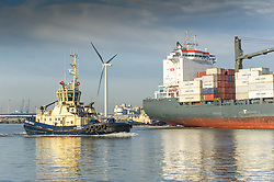 The tug, Switzer Bootle preparing to escort the container cargo ship, Pomerenia Sky as she leaves the Port of Tilbury on the River Thames.