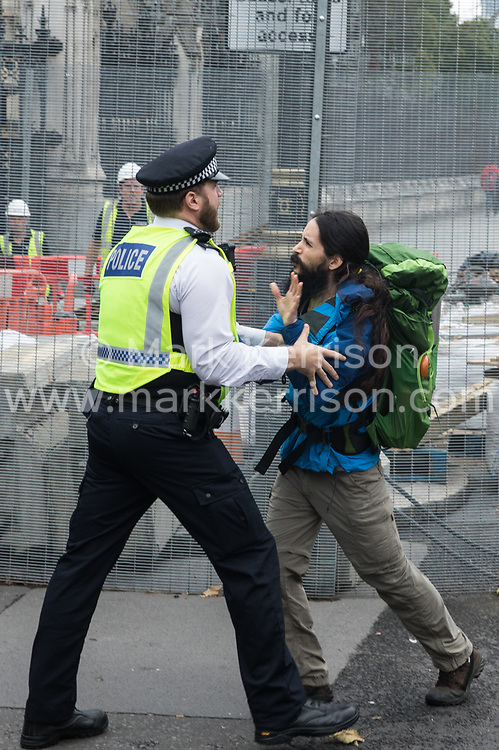 London, UK. 3rd September, 2020. A police officer prevents a climate activist from Extinction Rebellion from joining other activists who had glued themselves to the pavement outside the Houses of Parliament. Extinction Rebellion activists are attending a series of September Rebellion protests around the UK to call on politicians to back the Climate and Ecological Emergency Bill (CEE Bill) which requires, among other measures, a serious plan to deal with the UK's share of emissions and to halt critical rises in global temperatures and for ordinary people to be involved in future environmental planning by means of a Citizens' Assembly.