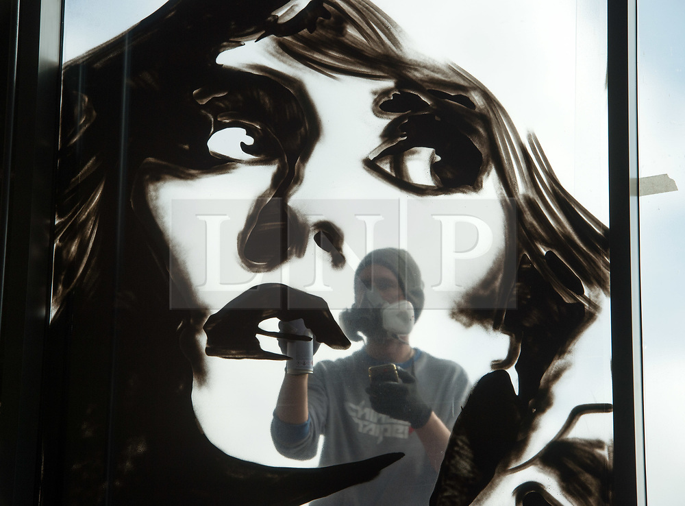 © Licensed to London News Pictures.  18/09/2017; Bristol, UK. VOYDER paints an image of Debbie Harry from Blondie onto the front window of the Colston Hall. Colston Hall, Bristol's largest music venue, is to unveil a new mural painted in partnership with Upfest by Bristol artist Voyder of eight musical legends, each of which have performed at Colston Hall over the last 150 years, to celebrate the Colston Hall's 150th anniversary this week on 20 September.   The giant mural on the glass panes above the main entrance will feature portraits of Ella Fitzgerald, Louis Armstrong, David Bowie, Debbie Harry (Blondie), Jimi Hendrix, Mick Jagger, Sergei Rachmaninoff and Paul McCartney. The mural will be in place in time for Colston Hall to mark its anniversary with a big free Birthday Bash on Wednesday 20 September, exactly 150 years from when the venue first opened, to which all of Bristol is invited. Highlights for the night will include the world-famous Ukulele Orchestra of Great Britain, immersive projections from Limbic Cinema and toe tapping swing music from the Bruce/Ilett Big Band. The free event will begin at 6.30pm and see a complete takeover of the building, giving people the chance to explore every corner, stumbling across musicians, DJs, installations and projections, as acts pop up to create a unique party atmosphere. Colston Hall first opened its doors to the public on the 20th September 1867, after The Colston Hall Company bought the land from Colston Boy's School in 1861 to fulfil their vision of building a concert hall in the city. The Hall has seen four iterations in its 60 years, with the fourth and present Colston Hall opening in 1951. Picture credit : Simon Chapman/LNP