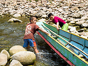 """Two Laoseng ethnic minority boys, Sone (13) and Sengpheth (10) push a boat through a channel made by the local boatmen to assist navigation of the Nam Ou river during the dry season when the river level is low, Phongsaly province, Lao PDR. The Nam Ou river connects small riverside villages and provides the rural population with food for fishing. It is a place where children play and families bathe, where men fish and women wash their clothes. But this river and others like it, that are the lifeline of rural communities and local economies are being blocked, diverted and decimated by dams. The Lao government hopes to transform the country into """"the battery of Southeast Asia"""" by exporting the power to Thailand and Vietnam."""