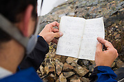 Brian Polagye holds open and reads the climbing register on the summit of Tomyhoi Peak, Mount Baker Wilderness, Washington.