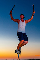 Street busker juggling fire, sharp knives and axe at sunset celebration, Mallory Square, Key West, Florida Keys, Florida USA