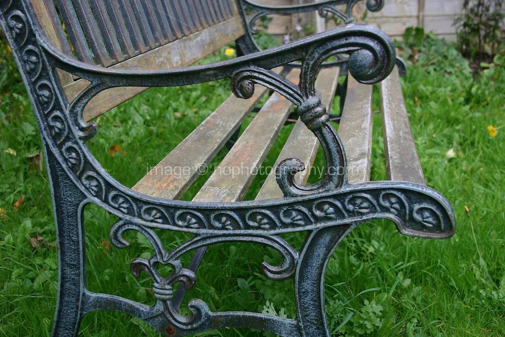Wooden garden bench on grass in Irish garden<br />