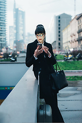 February 24, 2017 - Businesswoman with trolley luggage using mobile waiting by wall, Milan, Italy (Credit Image: © Eugenio Marongiu/Image Source via ZUMA Press)