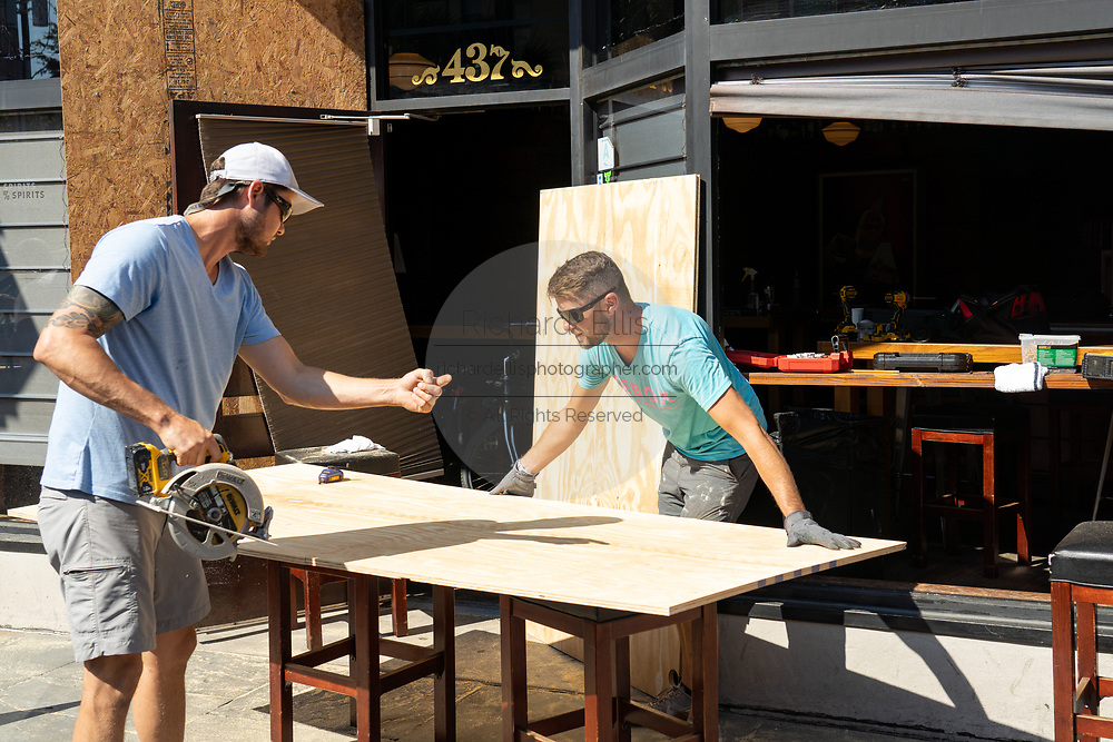 Charleston, United States. 31 May, 2020. Volunteers help replace broken windows with plywood boards at a restaurant along the King Street shopping district after a protest over the death of George Floyd, turned violent and destructive May 31, 2020 in Charleston, South Carolina. Floyd was choked to death by police in Minneapolis resulting in protests sweeping across the nation.  Credit: Richard Ellis/Alamy Live News