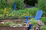 63821-21815 Flower garden with stone path, blue Adirondack chair and bird house. sedums, raspberry blast petunia and diamond frost euphorbia in blue pot, Butterfly Bushes, Joe Pye Weed (Eupatorium purpurea), Peach & Purple Verbenas, Yellow Lantana (Lantana camara), Karl Forster Grass, Marion Co., IL