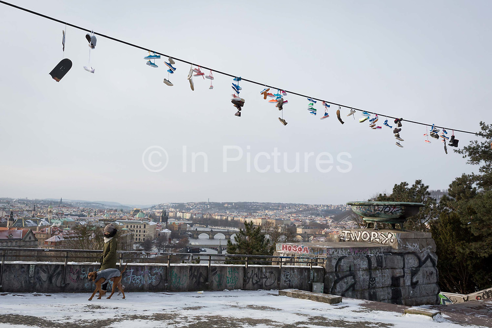 21st century shoes hang from cables above Stalinist-era architecture in Letna Park Letenske Sady, on 18th March, 2018, in Prague, the Czech Republic. Up until it was destroyed by Soviet leader Nikita Kruschev, the largest statue to Stalin in the entire Eastern Bloc was located here. It is now a favourite place skateboard park, dog walkers and families. Like Rome, Prague is built on seven hills.