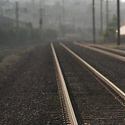 Railroad tracks leading away in distance in urban setting.