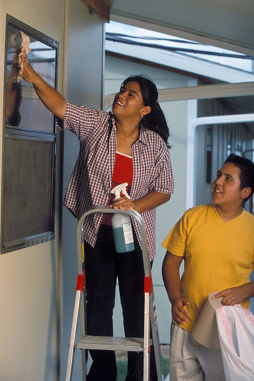 African-American and Hispanic Middle School teenagers wash windows in Pflugerville, Texas.  Model Release.<br /> ©Bob Daemmrich