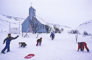 Children playing in the snow on ther farm near the village of Sudureyri, Iceland.
