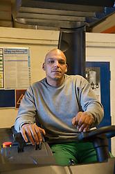 A prisoner working in a workshop driving a forklift, prison