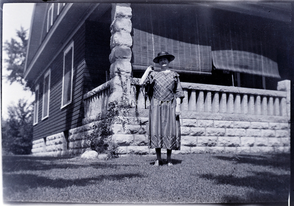 woman standing by house summer USA 1920s