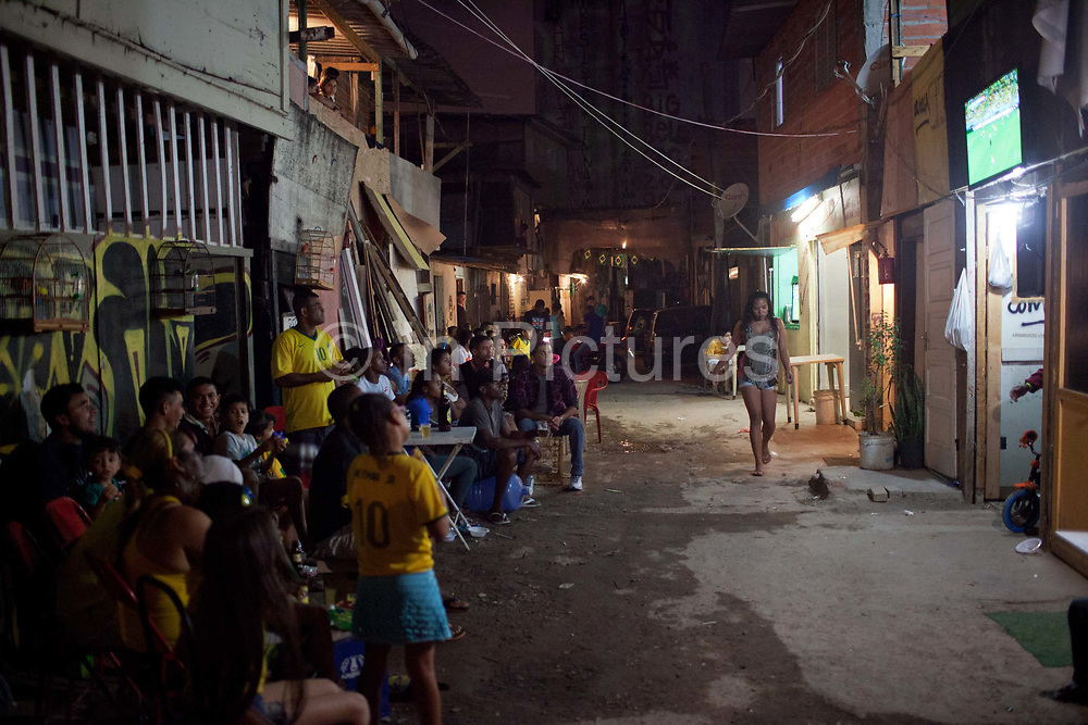 Supporters of the Brazilian national team, wearing green and yellow shirts, watch the opening game Brazil vs Croatia outdoors, tension in the air before gained the lead. Favela do Moinho, Sao Paulo, Brazil.