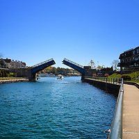 """""""Walking Charlevoix""""<br /> I always enjoy walking the lovely  walkways in Charlevoix Michigan. This time the drawbridge opened for a boat to pass through. A beautiful sight on a beautiful day!"""