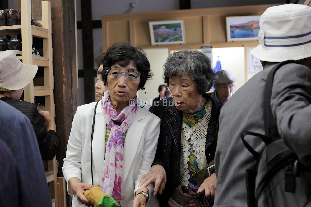 senior group traveling at entrance to a historical monument Japan