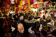 Inside a busy shop in Chinatown during Chinese New Year. London, UK. People crowd into the store to buy decorations.