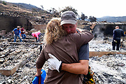 Craig Bolleson of home owner, hugs his friend in his burned out home, Monday, Sept. 4, 2017, in the Sunland-Tujunga section of Los Angeles.