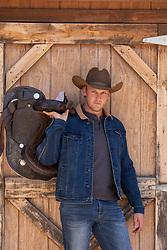 handsome blond cowboy by a rustic barn door
