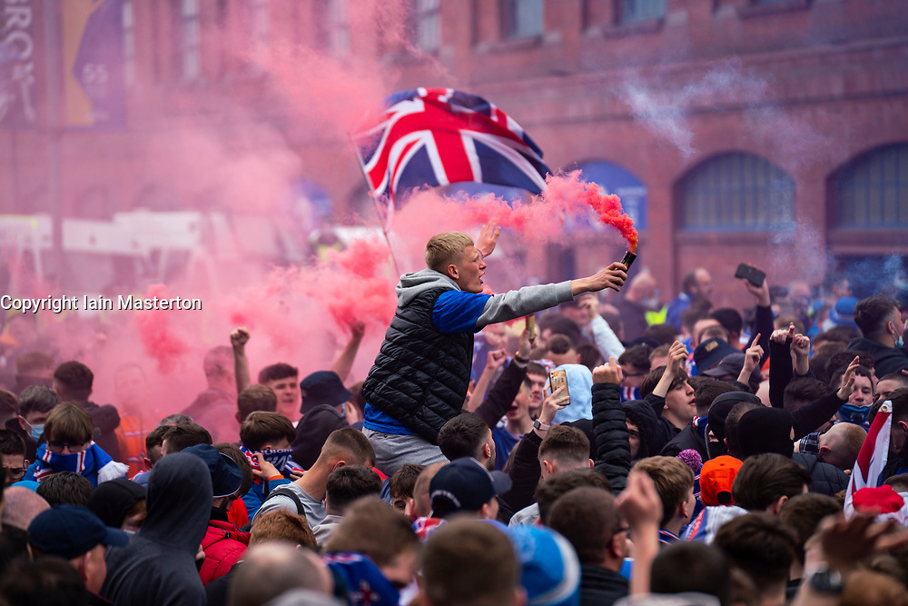 Glasgow, Scotland, UK. 15 May 2021. Thousands of supporters and fans of Rangers football club descend on Ibrox Park in Glasgow to celebrate winning the Scottish Premiership championship for the 55nd time and the first time for 10 years. Smoke bombs and fireworks are being let off by fans tightly controlled by police away from the stadium entrances.Iain Masterton/Alamy Live News