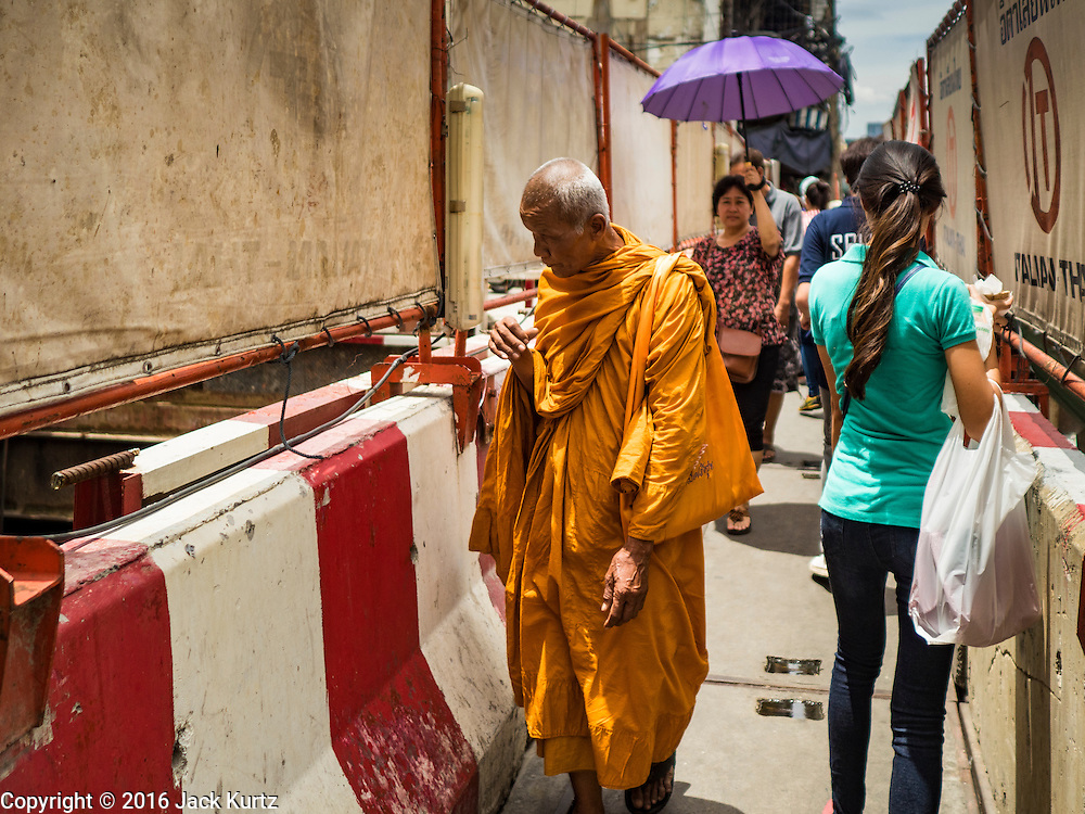 08 JUNE 2016 - BANGKOK, THAILAND:  A Buddhist monk looks into the subway construction at the intersection of Phlap Phla Chai and Chareon Krung Streets in Bangkok's Chinatown neighborhood. The Bangkok Metropolitan Rapid Transit (MRT) system, Bangkok's subway, is being expanded through Chinatown and a station is under construction at the intersection. The small produce market at the intersection will have to move and several of the businesses near the intersection have been evicted to make way for the construction. Bangkok's Chinatown, considered by some to be one of the best preserved Chinatown districts in the world, is changing. Many of the old shophouses are being demolished and replaced by malls and condominium developments.     PHOTO BY JACK KURTZ