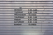 A small shop's business hours on lowered shutters in Harrogate, North Yorkshire. Listed on the metal surface, we see the days of the week along with corresponding hours of trading and the days it closes eg. Sunday Opening hours strictly follow trading laws in the UK. Small shops in England and Wales can open any day or hour. There are no trading hours restrictions in Scotland. Shops over 280 square metres: It can open on Sundays but only for 6 consecutive hours between 10am and 6pm. It must close on Easter Sunday and Christmas Day.