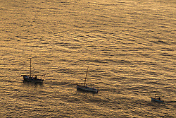 Sorrento, Italy, September 16 2017. Three boats make their way back to port as the last rays of the sun illuminate the water in Sorrento, Italy. © Paul Davey
