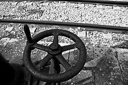 grossa manovella utilizzata per far scorrere da una bocca laterale dell'acqua atta a raffreddare le le caldaie dei vecchi treni, oramai in disuso. Reportage che racconta le situazioni che si incontrano durante un viaggio lungo le linee ferroviarie SUD EST nel Salento.