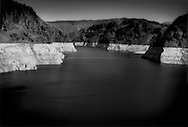 """Lake Mead's """"bathtub ring"""": Lake Mead, after several years of drought, is at 43% capacity (as of May 2009) because it is the primary source of water for Las Vegas and large sections of northern Arizona which continually draw water from the reservoir, Nevada / Arizona border, USA.  Lake Mead is the largest reservoir in the United States.  Researchers at Scripps Institution of Oceanography at the University of California-San Diego warn that, at current use levels and declining Rocky Mountains snowmelt, that there is a 50/50 chance that Lake Mead could be dry by 2021."""