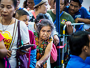 18 SEPTEMBER 2017 - BANGKOK, THAILAND: A woman in line for free food at Poh Teck Tung. The Ghost Festival, also known as the Hungry Ghost Festival, Zhongyuan Festival or Yulan Festival is a traditional Buddhist and Taoist festival held in Asian countries. According to the Chinese calendar (a lunisolar calendar), the Ghost Festival is on the 15th night of the seventh month. In Chinese culture, the fifteenth day of the seventh month in the lunar calendar is called Ghost Day and the seventh month in general is regarded as the Ghost Month, in which ghosts and spirits, including those of the deceased ancestors, come out from the lower realm. Distinct from both the Qingming Festival (in spring) and Double Ninth Festival (in autumn) in which living descendants pay homage to their deceased ancestors, during Ghost Festival, the deceased are believed to visit the living.     PHOTO BY JACK KURTZ