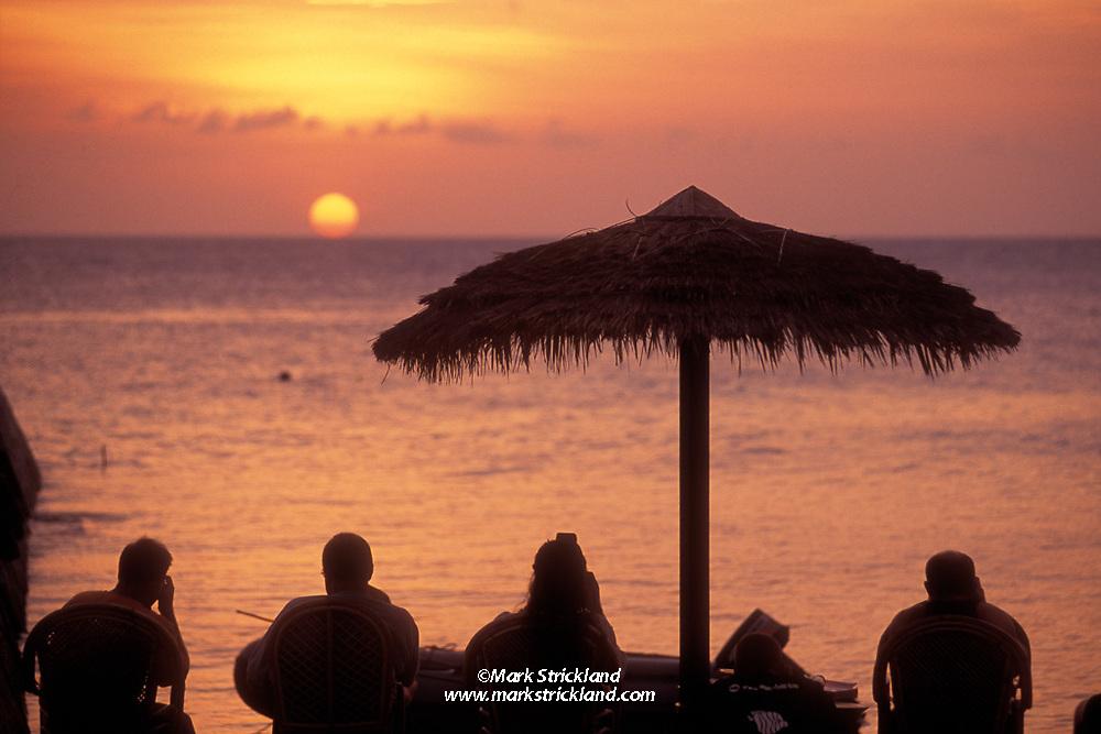 A group of divers enjoy some relaxing topside moments at sunset. Wakatobi Resort, Wakatobi Marine Preserve; Tukang Besi Islands; Flores Sea; Indonesia