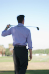 soft focus of a businessman golfing at a driving range